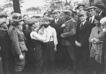 A GROUP of German soldiers and civilians look on as a Jewish man is forced to cut the beard of anoth