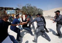 An Israeli policeman grabs an activist in the Palestinian Bedouin village of Khan al-Ahmar in the We