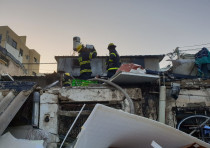 Firefighters at the burnt home of a 62-year-old woman killed in a fire in Tel Aviv's Carmel Market o