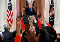 U.S. President Donald Trump points to a questioner while taking questions during a news conference