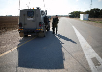 An Israeli soldier stands next to an armoured vehicle in kibbutz Nahal Oz