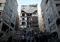 Palestinians gather near the remains of a building that was completely destroyed by an Israeli air s
