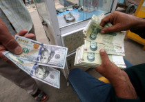 Iranian rials, U.S. dollars and Iraqi dinars at a currency exchange shop in Basra, Iraq, November 3,