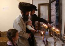 Lighting Hanukkah candles in Jerusalem's Mea She'arim neighborhood