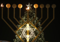 A giant menorah stands in front of a Christmas tree at the Brandenburg gate to celebrate Hanukkah in