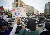 "A woman holds a sign which reads ""Boycott Israel"" in front of symbolic coffins while attending a dem"