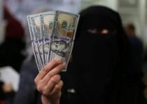 A Palestinian Hamas-hired civil servant displays U.S. Dollar banknotes