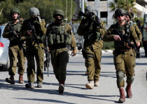 Israeli soldiers walk during clashes with Palestinians in Ramallah in the occupied West Bank, 2018.