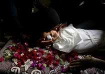 VISUAL COVERAGE OF SCENES OF INJURY OR DEATH A relative kisses the body of Palestinian boy Ahmed Ab
