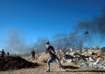 A Palestinian uses a sling to hurl stones during clashes with Israeli troops near the Jewish settlem