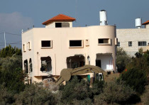 Israeli forces demolish part of the family house of Palestinian gunman Ashraf Naalwa in the village