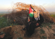 A PALESTINIAN woman takes cover during a protest at the Israel-Gaza border fence on Friday