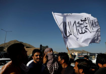 A member of the Taliban holds a flag in Kabul, Afghanistan