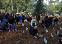 Participants planting trees in front of the memorial for victims of terror attacks in Buenos Aires.