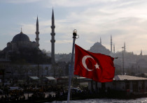 A Turkish flag, with the New and the Suleymaniye mosques in the background
