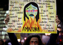 A protester holds a sign with the names of various indigenous tribes during a demonstration to deman