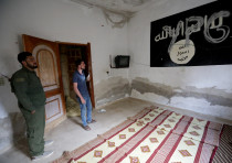 YPG (Kurdish People's Protection Units) is written over a wall painting of ISIS flag inside a house,
