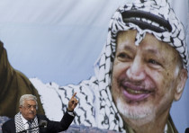 Palestinian President Mahmoud Abbas gestures beneath a poster of the late leader Yasser Arafat