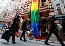 Riot police, with a rainbow flag in the background, chase LGBT rights activists in Istanbul, Turkey