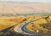 Vehicles drive along a road in the Jordan Valley