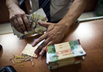 A bank employee counts Israeli Shekel notes for the camera at a bank branch in Tel Aviv