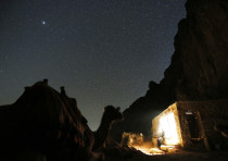 A tourist rests next to a camel under the stars near the summit of Mount Sinai
