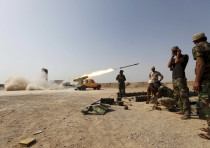 Shi'ite fighters fire a rocket toward Islamic State militants in Baiji, north of Baghdad, 2015