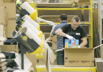 A WORKER packs completed orders at an Amazon fulfilment center. These simple brown boxes have ignite