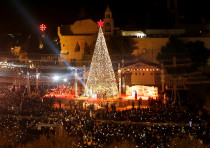 Palestinians light Christmas tree in Manger Square outside the Church of the Nativity in Bethlehem,