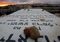 Stones placed in remembrance lie on grave tablets on the Mount of Olives Jewish cemetary as the sun