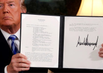 U.S. President Donald Trump holds up a proclamation declaring his intention to withdraw from the JCP