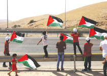 WHO WILL rule this? Palestinians wave flags at traffic on Highway 1 leading to the Dead Sea
