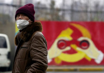 A man wears a mask as he walks past a mural showing a modified image of the Chinese Communist Party
