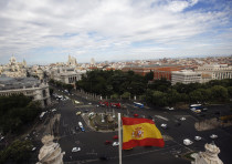 A Spanish flag flutters in the air as the capital of Spain is seen from the observatory deck of Madr