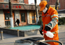 A street cleaner wearing a face mask sanitizes trash cans at a sidewalk, as the country is hit by an