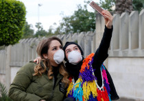 People wearing face masks take a picture with a mobile phone outside Rafik Hariri hospital in Beirut