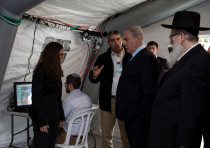 Israeli Prime Minister Benjamin Netanyahu arrives to a tent during his visit to the Chaim Sheba Medi