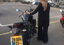 AMNEH HEBE, a Kabul resident, takes a break during motorcycle practice at the Western Galilee villag