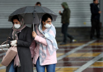 Iranian women wear protective masks to prevent contracting coronavirus, as they walk in the street i