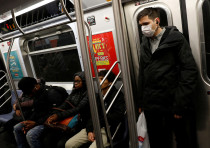 A man in a face mask rides the subway in Manhattan, New York City, after further cases of coronaviru