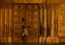 A worshippers stands in front of the closed entrance door of the Church of the Holy Sepulchre in Jer