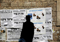 A Jewish ultra-Orthodox man looks onto a local billboard with instructions related to the coronaviru