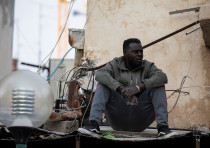 An African migrant sits near the Old Central Bus Station in south Tel Aviv, Israel February 3, 2020