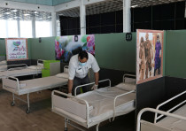 A medical aid worker sets up and installs a bed at a shopping mall which has been turned into a cent