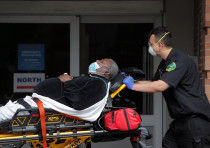 Paramedics take a patient into emergency center at Maimonides Medical Center during the outbreak of