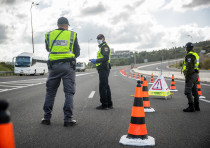 "Police at a temporary ""checkpoint"" on road number 1 outside Jerusalem on April 8, 2020, to check if"