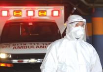 An MDA medic wearing protective gear against coronavirus waits outside Shaare Zedek Hospital, Jerusa