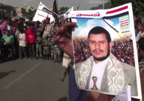A Houthi holds up an image of Abdul-Malik Badreddin al-Houthi, the movement leader, during protests