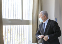 Prime Minister Benjamin Netanyahu looking out a barred window