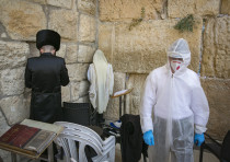 An Orthodox Jewish Talmudic seminary student wearing protective suit, gloves, face mask and a face s